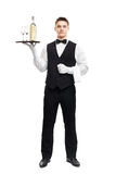 Young waiter with bottle of wine on tray Royalty Free Stock Photography