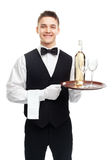 Young waiter with bottle of wine on tray Stock Images