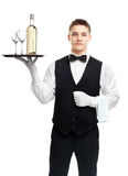 Young waiter with bottle of wine on tray Royalty Free Stock Photos