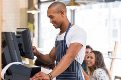 Young waiter doing bill. Happy young waiter in blue apron checking bill before printing it. Young african waiter printing bill in cafeteria. Waiter printing Royalty Free Stock Images