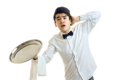 The young waiter with an empty tray for cupboards opened his mouth and kept the ball for a head Royalty Free Stock Photography