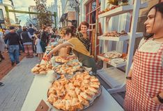 Young waiter girls selling cookies, cakes of a backery during a street festival