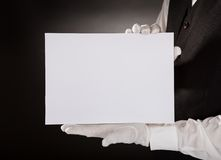Young waiter holding blank placard. Closeup Of Young Waiter Presenting Blank Placard Over Black Background Stock Image