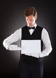 Young Waiter Holding Blank Placard. Young Waiter Presenting Blank Placard Over Black Background Royalty Free Stock Photography