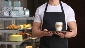 Young waiter holding tray with glass of coffee. At workplace Royalty Free Stock Photography