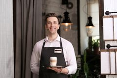 Young waiter holding tray with glass of coffee. At workplace Stock Image