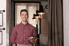 Young waiter holding tray with tasty dish. At workplace Royalty Free Stock Photo