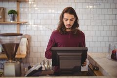 Young waiter with long hair using cash register at coffee shop. Young waiter with long hair using cash register against wall at coffee shop Stock Photos