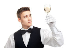 Young waiter looking at the glass filled with white wine Royalty Free Stock Photo