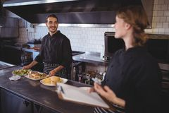 Young waiter preparing food while looking at waitress. In coffee shop Royalty Free Stock Images