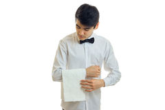 A young waiter`s shirt carefully hangs towel on hand. Isolated on white background close-up Stock Images