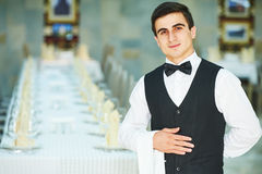 Young waiter at service in restaurant. Male cheerful waiter in restaurant readu to service Stock Photo