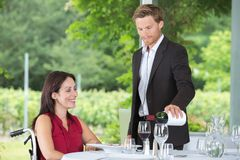 Young waiter serving mature disabled woman at restaurant Royalty Free Stock Photography