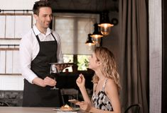 Young waiter serving wine to client. In restaurant stock photography