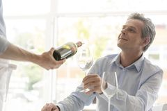 Young waiter serving wine to mature customer at restaurant stock images