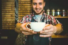 Young waiter smiling and holding cup of coffee. At the cafe Royalty Free Stock Image