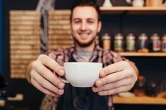 Young waiter smiling and holding cup of coffee. At the cafe Royalty Free Stock Photo