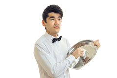 The young waiter surprised looks to the side and rubs towel tray is isolated on a white background Royalty Free Stock Photos