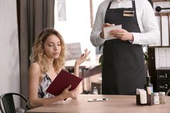 Young waiter taking order from client. In restaurant Royalty Free Stock Photos
