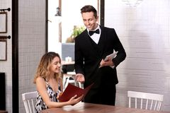 Young waiter taking order from client. In restaurant Royalty Free Stock Images