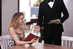 Young waiter taking order from client. In restaurant Stock Image