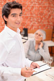 Young waiter taking an order. In a restaurant Royalty Free Stock Photos
