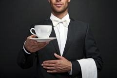 Young waiter in uniform serving hot coffee stock images