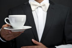 Young waiter in uniform serving hot coffee Royalty Free Stock Photo