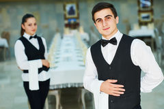 Young waiter and waitress at service in restaurant. Waiter and waitress restaurant catering service. Male cheerful restaurant worker with women at background Royalty Free Stock Photos