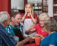 Young Waitress and Arguing Seniors Royalty Free Stock Photos