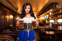 Young waitress brings beer to visitors. Oktoberfest. Sexy woman in dirndl dress holding Oktoberfest beer stein Stock Photography