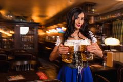 Young waitress brings beer to visitors Stock Photo