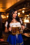 Young waitress brings beer to visitors Stock Image