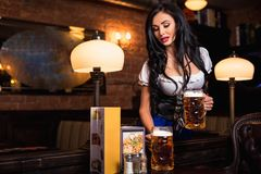 Young waitress brings beer to visitors Stock Photos