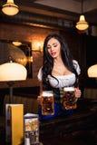 Young waitress brings beer to visitors Royalty Free Stock Image