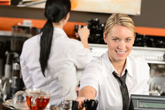 Young waitress cashier giving coffee in cafe Stock Photo