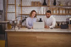 Young waitress and male owner using laptop at counter Royalty Free Stock Photos