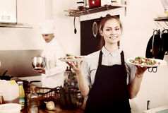 Young waitress with served salad on kitchen Stock Photo