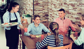 Young waitress serving family in family cafe stock image