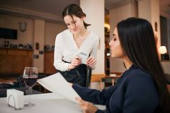 Young waitress stand besides sitting customer and look at menu she point. Businesswoman talking to her. They are in stock photos