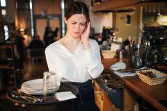 Young waitress suffer from headache. She hold hand on head. Also young woman hold stray with plates. She stand at bar. royalty free stock photo