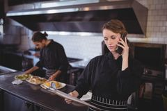 Young waitress talking on smartphone while waiter preparing food in commercial kitchen. At coffee shop Royalty Free Stock Photography