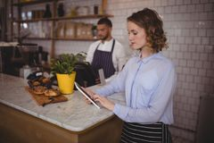 Young waitress using tablet computer while standing at counter Stock Images