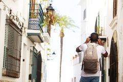 Young wan walking with bag and headphones Stock Images