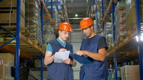 A young warehouse employee leans from an experiences colleague. stock footage