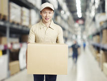 Young warehouse worker carrying a carton box Stock Photo