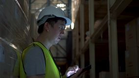 Young warehouse worker man with safety hard hat is checking order details with a digital tablet at inventory room