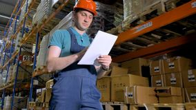 A young warehouse worker walks and takes note on paper. stock video footage