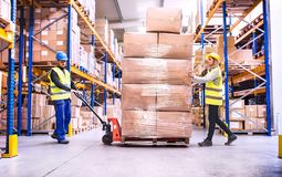 Warehouse workers pulling a pallet truck. Young warehouse workers pulling a pallet truck with boxes stock photo