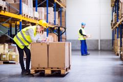 Young warehouse workers with smartphone. Young women warehouse worker with smartphone, making a phone call. A men worker holding a box Royalty Free Stock Photo